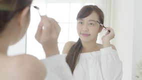 Beautiful young asian woman applying makeup eyebrows brush, beauty asia girl using cosmetic for make-up style