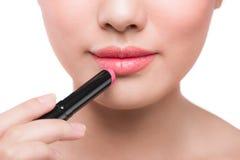Beautiful young asian woman applying pink lipstick Stock Photo