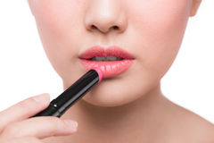 Beautiful young asian woman applying pink lipstick Royalty Free Stock Photo