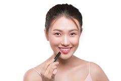 Beautiful young asian woman applying pink lipstick Stock Photos