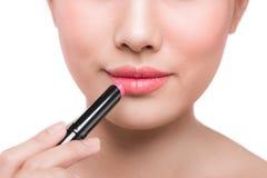 Beautiful young asian woman applying pink lipstick Royalty Free Stock Photography