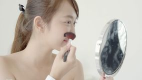 Beautiful young asian woman applying powder with brush looking mirror, beauty girl makeup face with blush cosmetic