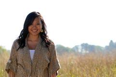 Beautiful young Asian woman - Autumn. Beautiful young Asian woman wearing sweater standing in field Stock Image