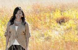 Beautiful young Asian woman - Autumn. Beautiful young Asian woman wearing sweater standing in field royalty free stock image