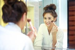 Beautiful young asian woman in bathrobe applying makeup stock photos