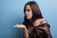 Beautiful young Asian woman blow a kiss. Beautiful young Asian woman blow a kiss on blue background Royalty Free Stock Images