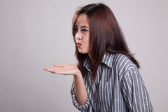 Beautiful young Asian woman blow a kiss. Beautiful young Asian woman blow a kiss on gray background Stock Image