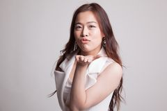 Beautiful young Asian woman blow a kiss. Beautiful young Asian woman blow a kiss on gray background Royalty Free Stock Images