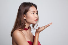 Beautiful young Asian woman blow a kiss. Beautiful young Asian woman blow a kiss on gray background Stock Photos
