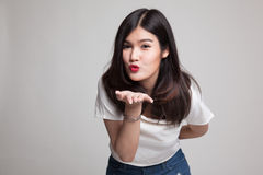 Beautiful young Asian woman blow a kiss. Beautiful young Asian woman blow a kiss on gray background Royalty Free Stock Photography