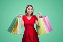 Beautiful young asian woman with colored shopping bags over blue Royalty Free Stock Photos