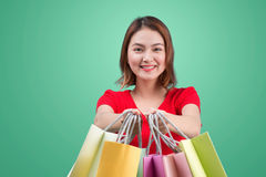 Beautiful young asian woman with colored shopping bags over blue Royalty Free Stock Photography