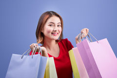 Beautiful young asian woman with colored shopping bags over blue Stock Photo