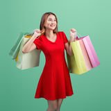 Beautiful young asian woman with colored shopping bags over blue Royalty Free Stock Photo
