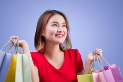 Beautiful young asian woman with colored shopping bags over viol. Et background Royalty Free Stock Photography