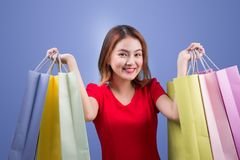 Beautiful young asian woman with colored shopping bags over viol. Et background Stock Images