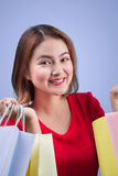 Beautiful young asian woman with colored shopping bags over viol. Et background Royalty Free Stock Image