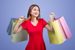 Beautiful young asian woman with colored shopping bags over viol. Et background Royalty Free Stock Photos