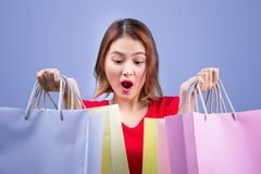 Beautiful young asian woman with colored shopping bags over viol. Et background Stock Photo