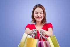 Beautiful young asian woman with colored shopping bags over viol. Et background Royalty Free Stock Photo
