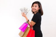 Beautiful young Asian woman with colorful shopping bags. One han. D holds money one hundred dollar bill on white background royalty free stock images