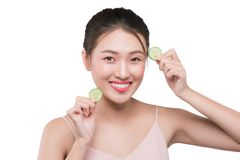 Beautiful young asian woman with cucumber slices stock image