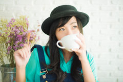 Beautiful young Asian woman with cup of coffee Stock Photo