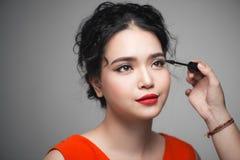 Beautiful young asian woman doing makeup using mascara on her ey Stock Photo