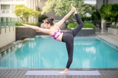 Young Asian woman doing yoga exercise near swimming pool Stock Images