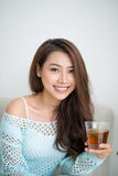 Beautiful young asian woman drinking her morning tea over a brea Stock Photography