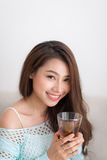 Beautiful young asian woman drinking her morning tea over a brea Royalty Free Stock Images