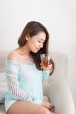 Beautiful young asian woman drinking her morning tea over a brea Stock Photo