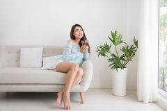 Beautiful young asian woman drinking her morning tea over a brea Royalty Free Stock Photos