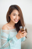 Beautiful young asian woman drinking her morning tea over a brea Stock Photos