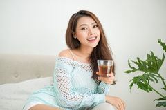 Beautiful young asian woman drinking her morning tea over a brea Royalty Free Stock Image