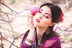 Beautiful young Asian woman enjoying the scent of magnolia blossoms. Beautiful young Asian woman closed her eyes and enjoying the scent of magnolia blossoms. She royalty free stock image