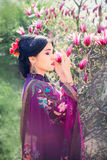 Beautiful young Asian woman enjoying the scent of magnolia blossoms. Beautiful young Asian woman closed her eyes and enjoying the scent of magnolia blossoms stock image