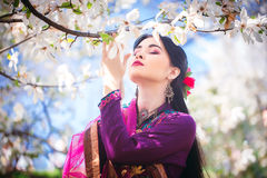 Beautiful young Asian woman enjoying the scent of magnolia blossoms. Beautiful young Asian woman closed her eyes and enjoying the scent of magnolia blossoms royalty free stock photos