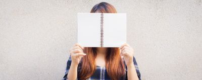 Beautiful young asian woman hiding behind a blank mock up book on concrete wall background. Vintage effect style pictures. Panoramic banner Stock Images