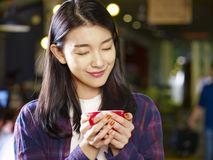 Beautiful young asian woman holding a cup of coffee. Smiling with eyes closed Royalty Free Stock Images