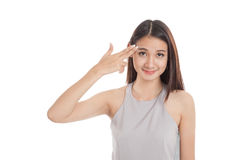 Beautiful young Asian woman holding fingers in gun gesture Royalty Free Stock Photos