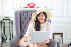 Beautiful young  asian woman at home sitting on luxury sofa  usi Royalty Free Stock Photos