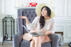 Beautiful young  asian woman at home sitting on luxury sofa  usi Stock Photo