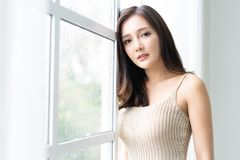 Free Beautiful Young Asian Woman Leaning At The Glass Window With Rain Drops And Looking At Camera At Her Home. Morning. Mood. Royalty Free Stock Image - 160589826