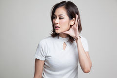 Beautiful young Asian woman listen to something. Beautiful young Asian woman listen to something on gray background Stock Photo