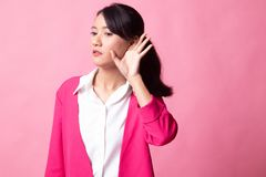 Beautiful young Asian woman listen to something. On pink background royalty free stock photography