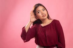 Beautiful young Asian woman listen to something. On pink background stock image