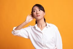 Beautiful young Asian woman listen to something. On yellow background stock photography