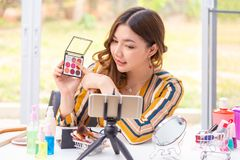 Beautiful young Asian woman making online product review at home stock photo