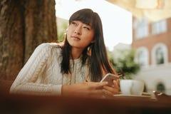 Beautiful young asian woman at outdoor cafe Stock Photos